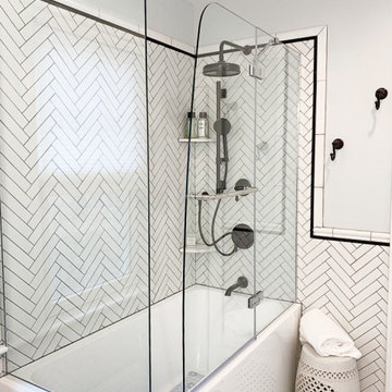 Corner Porcelain Tub with Herringbone Backsplash and Black Trim