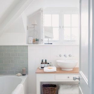 Inspiration for a small coastal ensuite bathroom in Cornwall with white walls, pebble tile flooring, wooden worktops, beige floors, brown worktops, freestanding cabinets, white cabinets, an alcove bath, green tiles, metro tiles and a vessel sink.