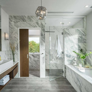 Modelo de cuarto de baño actual con armarios con paneles lisos, puertas de armario de madera en tonos medios, bañera encastrada sin remate, ducha empotrada, baldosas y/o azulejos grises, lavabo de seno grande, suelo gris y ducha con puerta con bisagras