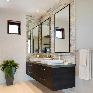 Modelo de cuarto de baño principal, minimalista, de tamaño medio, con armarios con paneles lisos, puertas de armario de madera en tonos medios, baldosas y/o azulejos beige, baldosas y/o azulejos marrones, baldosas y/o azulejos de cemento, paredes grises, suelo de baldosas de porcelana, lavabo sobreencimera, encimera de cemento, suelo beige y encimeras grises