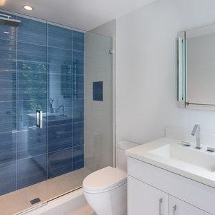 Esempio di una grande stanza da bagno per bambini minimalista con ante lisce, ante bianche, WC monopezzo, piastrelle blu, piastrelle di vetro, pareti bianche, pavimento in gres porcellanato, lavabo integrato, top in cemento, pavimento bianco e porta doccia scorrevole