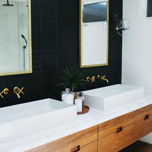 Immagine di una stanza da bagno padronale moderna di medie dimensioni con ante lisce, ante in legno bruno, doccia alcova, piastrelle nere, piastrelle in gres porcellanato, pareti bianche, lavabo a bacinella, top in marmo e porta doccia a battente