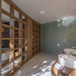 Modelo de cuarto de baño principal, contemporáneo, grande, con encimera de madera, armarios con paneles lisos, puertas de armario de madera oscura, bañera exenta, baldosas y/o azulejos azules, baldosas y/o azulejos en mosaico, paredes marrones, suelo de pizarra y lavabo sobreencimera