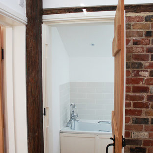 Inspiration for a small rustic family bathroom in Kent with shaker cabinets, white cabinets, a built-in bath, a shower/bath combination, a one-piece toilet, white tiles, porcelain tiles, white walls, vinyl flooring, a wall-mounted sink, solid surface worktops and beige floors.