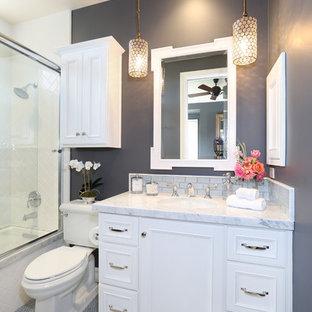 Imagen de cuarto de baño tradicional con bañera empotrada, combinación de ducha y bañera, sanitario de dos piezas, puertas de armario blancas y paredes grises