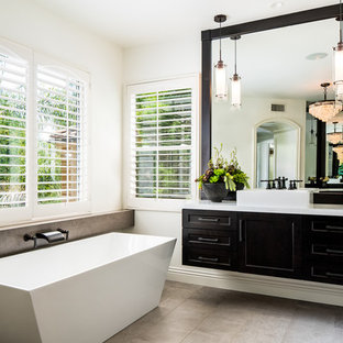 Transitional master gray floor freestanding bathtub photo in Orange County with shaker cabinets, black cabinets, white walls and a vessel sink