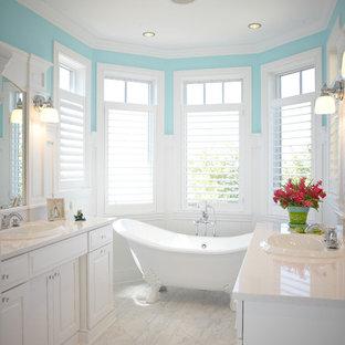 Foto di una grande stanza da bagno padronale tradizionale con lavabo da incasso, ante con bugna sagomata, ante bianche, vasca con piedi a zampa di leone, top in quarzite, WC a due pezzi, pareti blu, pavimento in marmo e pavimento bianco