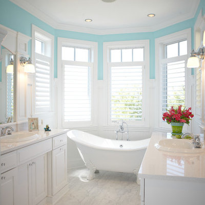 Claw-foot bathtub - large traditional master marble floor and white floor claw-foot bathtub idea in Grand Rapids with a drop-in sink, raised-panel cabinets, white cabinets, quartzite countertops, a two-piece toilet and blue walls