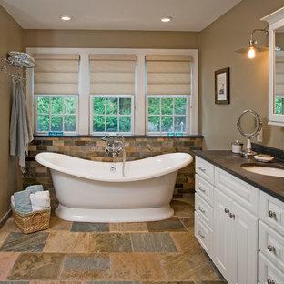 Ejemplo de cuarto de baño clásico con bañera exenta, lavabo bajoencimera y baldosas y/o azulejos de pizarra