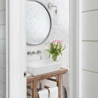Imagen de cuarto de baño costero con armarios tipo mueble, puertas de armario de madera oscura, paredes blancas, lavabo sobreencimera, encimera de madera, suelo blanco y encimeras marrones
