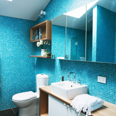 Large trendy master blue tile and mosaic tile ceramic tile bathroom photo in Melbourne with a vessel sink, flat-panel cabinets, white cabinets, wood countertops and a two-piece toilet