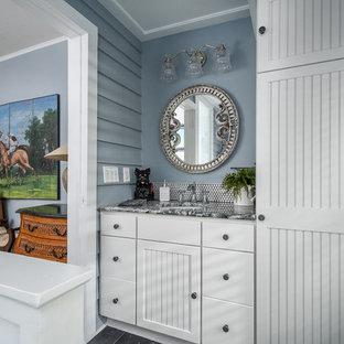 Diseño de cuarto de baño principal, costero, de tamaño medio, con armarios tipo mueble, puertas de armario blancas, bañera con patas, baldosas y/o azulejos blancos, baldosas y/o azulejos en mosaico, paredes azules, suelo de pizarra, lavabo bajoencimera, encimera de granito y suelo azul