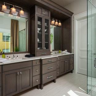 Immagine di una stanza da bagno padronale stile marinaro con consolle stile comò, ante in legno bruno, doccia a filo pavimento, piastrelle grigie, pareti beige, lavabo sottopiano, pavimento beige, porta doccia a battente e top beige