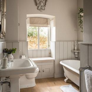 Пример оригинального дизайна: ванная комната среднего размера в классическом стиле с ванной на ножках, унитазом-моноблоком, серыми стенами, коричневым полом, фасадами с утопленной филенкой, белыми фасадами, паркетным полом среднего тона, душевой кабиной и раковиной с пьедесталом