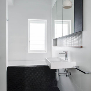 Contemporary bathroom in Perth with a drop-in tub, white tile, white walls, mosaic tile floors, a wall-mount sink and black floor.
