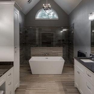 Идея дизайна: большая главная ванная комната в современном стиле с фасадами в стиле шейкер, белыми фасадами, отдельно стоящей ванной, душем в нише, раздельным унитазом, черной плиткой, серой плиткой, керамогранитной плиткой, серыми стенами, полом из керамогранита, врезной раковиной, столешницей из талькохлорита, коричневым полом и душем с распашными дверями