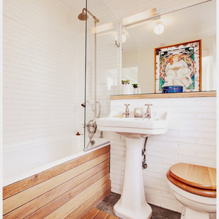 Farmhouse bathroom in London with a pedestal sink, an alcove bath, a shower/bath combination, a two-piece toilet, white tiles and white walls.