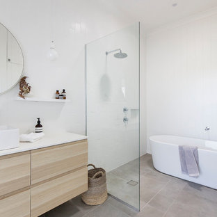 Inspiration for a large country master bathroom in Wollongong with a freestanding tub, an open shower, white tile, ceramic tile, white walls, engineered quartz benchtops, grey floor, white benchtops, flat-panel cabinets, light wood cabinets, a vessel sink and an open shower.