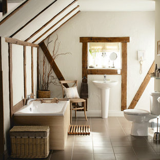 Farmhouse bathroom in West Midlands with a pedestal sink, a built-in bath, a two-piece toilet and white walls.