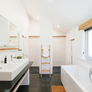This is an example of a rural ensuite bathroom in Cornwall with a freestanding bath, a built-in shower, white tiles, white walls, a vessel sink, grey floors, an open shower and black worktops.