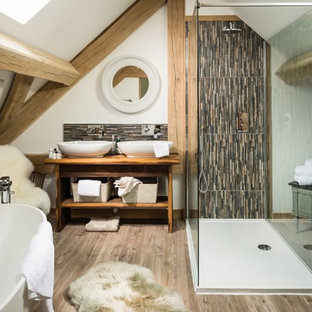 Inspiration for a large rural bathroom in Other with freestanding cabinets, a freestanding bath, ceramic tiles, white walls, light hardwood flooring, wooden worktops, beige floors, medium wood cabinets, multi-coloured tiles and a vessel sink.