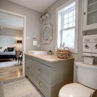Photo of a medium sized country family bathroom in Other with shaker cabinets, green cabinets, a two-piece toilet, grey walls, ceramic flooring, a vessel sink, wooden worktops, grey floors and beige worktops.