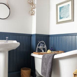 Photo of a small farmhouse family bathroom in Other with a freestanding bath, a two-piece toilet, blue walls, laminate floors, a pedestal sink and grey floors.