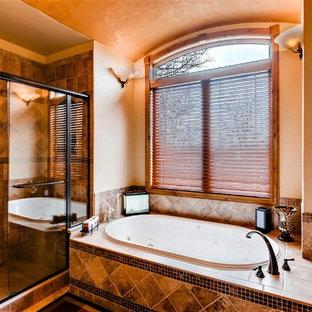 Ejemplo de cuarto de baño principal, de estilo americano, grande, con armarios con paneles con relieve, puertas de armario de madera oscura, bañera encastrada, ducha empotrada, sanitario de dos piezas, baldosas y/o azulejos beige, baldosas y/o azulejos de porcelana, paredes beige, suelo de baldosas de porcelana, lavabo bajoencimera, encimera de azulejos, suelo beige y ducha con puerta corredera
