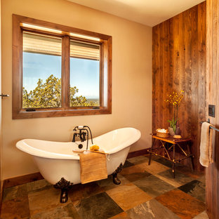 Large mountain style master gray tile and porcelain tile slate floor and brown floor bathroom photo in Other with recessed-panel cabinets, dark wood cabinets, beige walls, an undermount sink, granite countertops, a hinged shower door and gray countertops