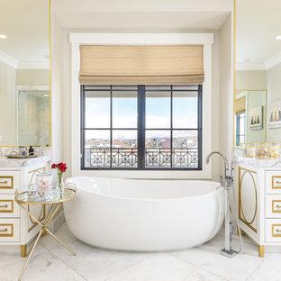 Esempio di un'ampia stanza da bagno padronale chic con ante bianche, vasca freestanding, pavimento bianco, ante con bugna sagomata, pareti beige, pavimento in marmo, lavabo integrato, top in marmo e top grigio