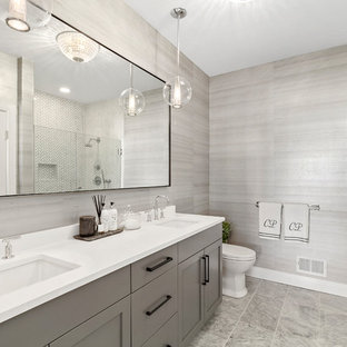 Inspiration for a transitional 3/4 gray tile gray floor alcove shower remodel in New York with shaker cabinets, gray cabinets, a two-piece toilet, beige walls, an undermount sink, a hinged shower door and white countertops