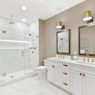 Inspiration for a transitional white tile white floor alcove shower remodel in New York with shaker cabinets, white cabinets, beige walls, an undermount sink, a hinged shower door and white countertops