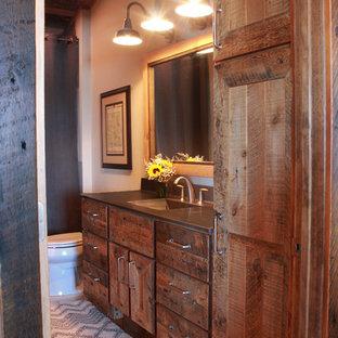 Immagine di una stanza da bagno padronale rustica di medie dimensioni con lavabo integrato, ante con riquadro incassato, ante con finitura invecchiata, top in cemento, vasca ad alcova, vasca/doccia, WC a due pezzi, pareti grigie e pavimento in pietra calcarea