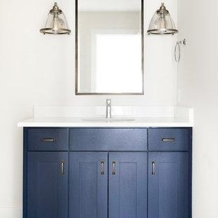 ミネアポリスの中サイズのトランジショナルスタイルのおしゃれな子供用バスルーム (シェーカースタイル扉のキャビネット、青いキャビネット、洗い場付きシャワー、アンダーカウンター洗面器、珪岩の洗面台、開き戸のシャワー、白い洗面カウンター、白いタイル、サブウェイタイル、白い壁、セラミックタイルの床、グレーの床、分離型トイレ) の写真
