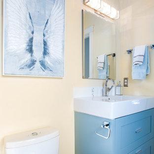 Idee per una piccola stanza da bagno padronale design con ante in stile shaker, ante turchesi, doccia alcova, WC monopezzo, piastrelle grigie, piastrelle di vetro, pareti gialle, pavimento in gres porcellanato e lavabo rettangolare