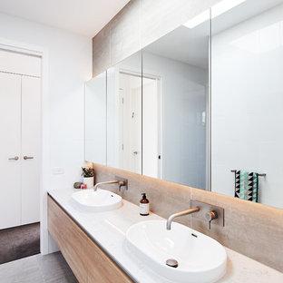 Foto di una grande stanza da bagno padronale contemporanea con ante lisce, ante in legno chiaro, vasca/doccia, piastrelle bianche, lastra di vetro, pareti grigie, pavimento con piastrelle in ceramica, lavabo da incasso, top in quarzo composito, pavimento grigio, doccia aperta e top bianco
