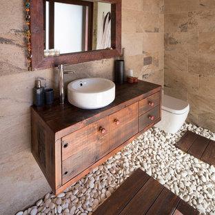 Bild på ett mellanstort orientaliskt brun brunt en-suite badrum, med ett fristående handfat, en vägghängd toalettstol, släta luckor, skåp i mörkt trä, beige kakel, stenhäll och träbänkskiva