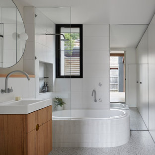 This is an example of a mid-sized contemporary 3/4 bathroom in Melbourne with flat-panel cabinets, medium wood cabinets, a drop-in tub, a shower/bathtub combo, a one-piece toilet, white tile, porcelain tile, white walls, an open shower, a console sink, grey floor and white benchtops.