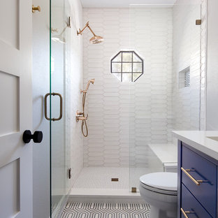 Small traditional shower room in Austin with flat-panel cabinets, blue cabinets, an alcove shower, white tiles, a submerged sink, multi-coloured floors, a hinged door, white worktops, porcelain tiles, cement flooring and solid surface worktops.