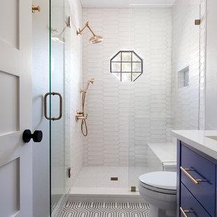 オースティンの小さいトランジショナルスタイルのおしゃれなバスルーム (浴槽なし) (フラットパネル扉のキャビネット、青いキャビネット、アルコーブ型シャワー、白いタイル、アンダーカウンター洗面器、マルチカラーの床、開き戸のシャワー、白い洗面カウンター、磁器タイル、セメントタイルの床、人工大理石カウンター) の写真