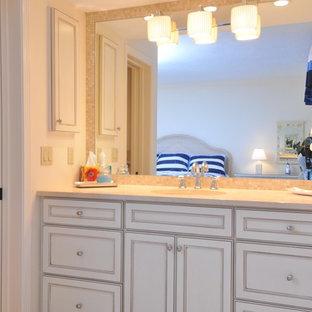 Esempio di una stanza da bagno padronale tropicale di medie dimensioni con ante con riquadro incassato, vasca ad alcova, doccia alcova, WC monopezzo, piastrelle beige, piastrelle multicolore, piastrelle in pietra, pareti beige, pavimento in travertino, lavabo sottopiano, top in granito e ante bianche