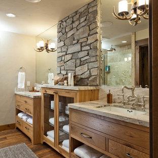 Idées déco pour une salle de bain principale montagne avec un placard à porte plane, des portes de placard en bois brun, un mur beige, un sol en bois foncé, un lavabo encastré et un sol marron.