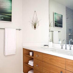 Idéer för små funkis badrum, med ett undermonterad handfat, släta luckor, skåp i mellenmörkt trä, bänkskiva i kvarts, ett badkar i en alkov, en dusch/badkar-kombination, en toalettstol med separat cisternkåpa, grå kakel, keramikplattor, vita väggar och klinkergolv i keramik