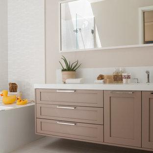 Modern inredning av ett badrum, med skåp i shakerstil, beige skåp, ett badkar i en alkov och vit kakel