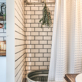 Modelo de cuarto de baño campestre con puertas de armario de madera en tonos medios, bañera exenta, baldosas y/o azulejos blancos, baldosas y/o azulejos de cemento, paredes blancas, suelo de madera oscura, lavabo encastrado, encimera de madera, suelo marrón, ducha con cortina y encimeras marrones