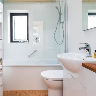 Small contemporary kids bathroom in London with flat-panel cabinets, white cabinets, an alcove tub, an alcove shower, a one-piece toilet, glass sheet wall, white walls, cork floors, a drop-in sink, wood benchtops, brown floor, a hinged shower door and brown benchtops.