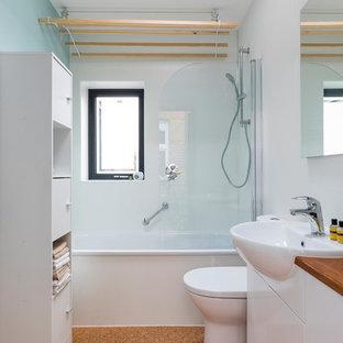 Idéer för små funkis brunt badrum för barn, med släta luckor, vita skåp, ett badkar i en alkov, en dusch i en alkov, en toalettstol med hel cisternkåpa, glasskiva, vita väggar, korkgolv, ett nedsänkt handfat, träbänkskiva, brunt golv och dusch med gångjärnsdörr