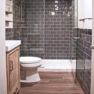 Ejemplo de cuarto de baño con ducha, tradicional renovado, pequeño, con armarios con paneles lisos, puertas de armario con efecto envejecido, ducha empotrada, sanitario de dos piezas, baldosas y/o azulejos grises, baldosas y/o azulejos de cerámica, paredes grises, suelo vinílico, lavabo integrado, ducha con puerta con bisagras y encimeras blancas