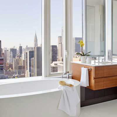 Freestanding bathtub - contemporary white floor freestanding bathtub idea in New York with flat-panel cabinets, medium tone wood cabinets, an undermount sink, white countertops and a floating vanity