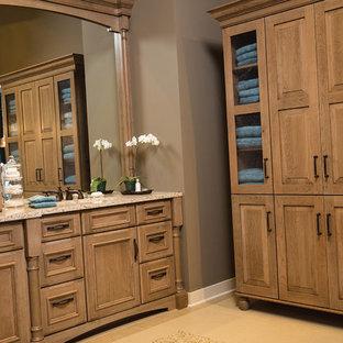 Imagen de cuarto de baño principal, tradicional, con armarios con paneles lisos, puertas de armario de madera clara, sanitario de una pieza, baldosas y/o azulejos beige, paredes beige, suelo vinílico, lavabo integrado y encimera de cuarcita